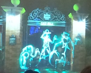 A light painting of the Hitchhiking Ghosts in front of The Haunted Mansion.