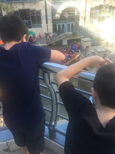 The boys are looking down at the Rio San Antonio Cruise boat from a balcony at Rivercenter Mall.